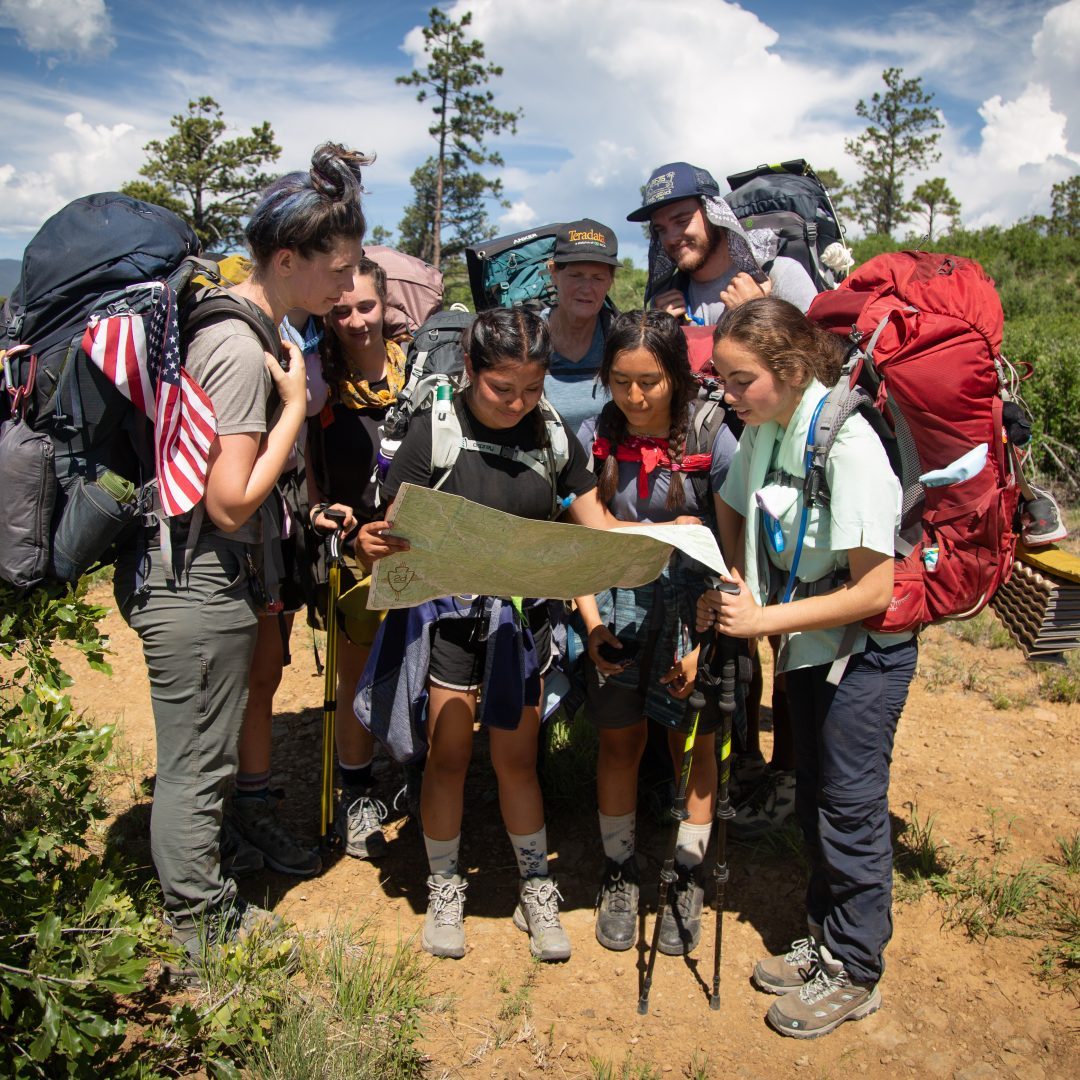 Members of crew 611-K front row: Isabelle DuPont- Moore, Sophia White (hidden), Grace Maready, Anita Richards, Ethan Boud, front row: Carolina Garcia, Elizabeth Nango and Jadyn Blake look at a map in front of Mount Baldy at Philmont Scout Ranch in Cimarron, New Mexico on Saturday, June 15, 2019.